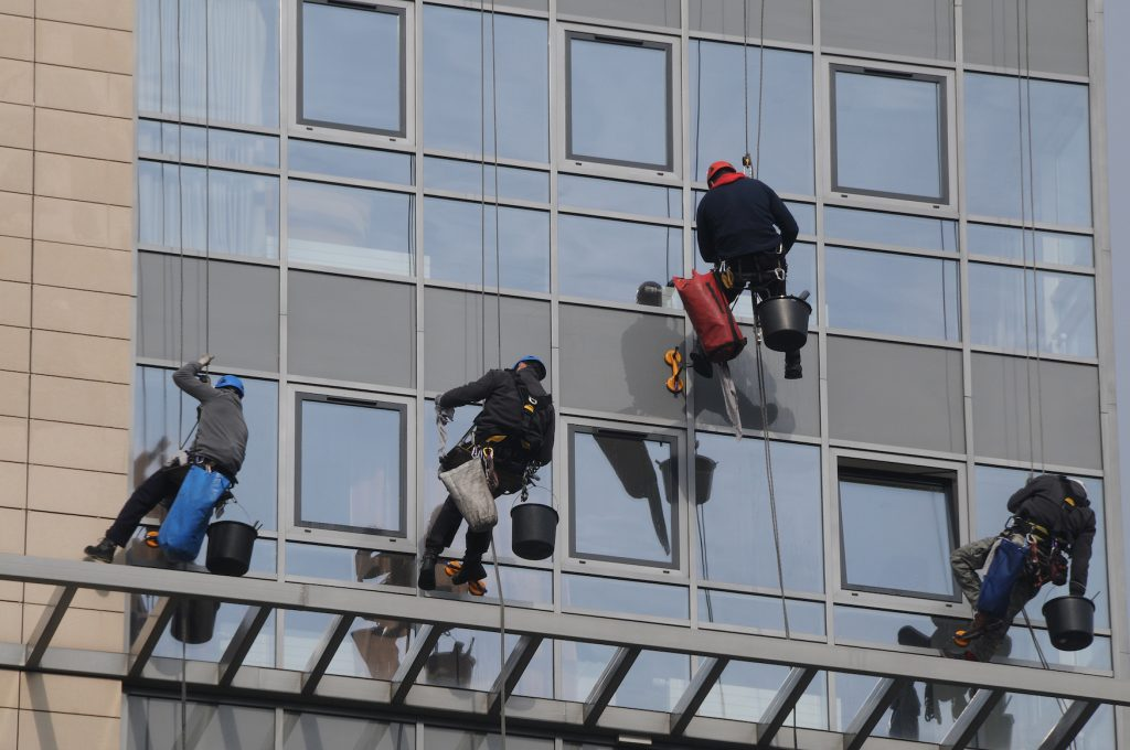 Maintenance workers climbing outside a skyscraper and clean